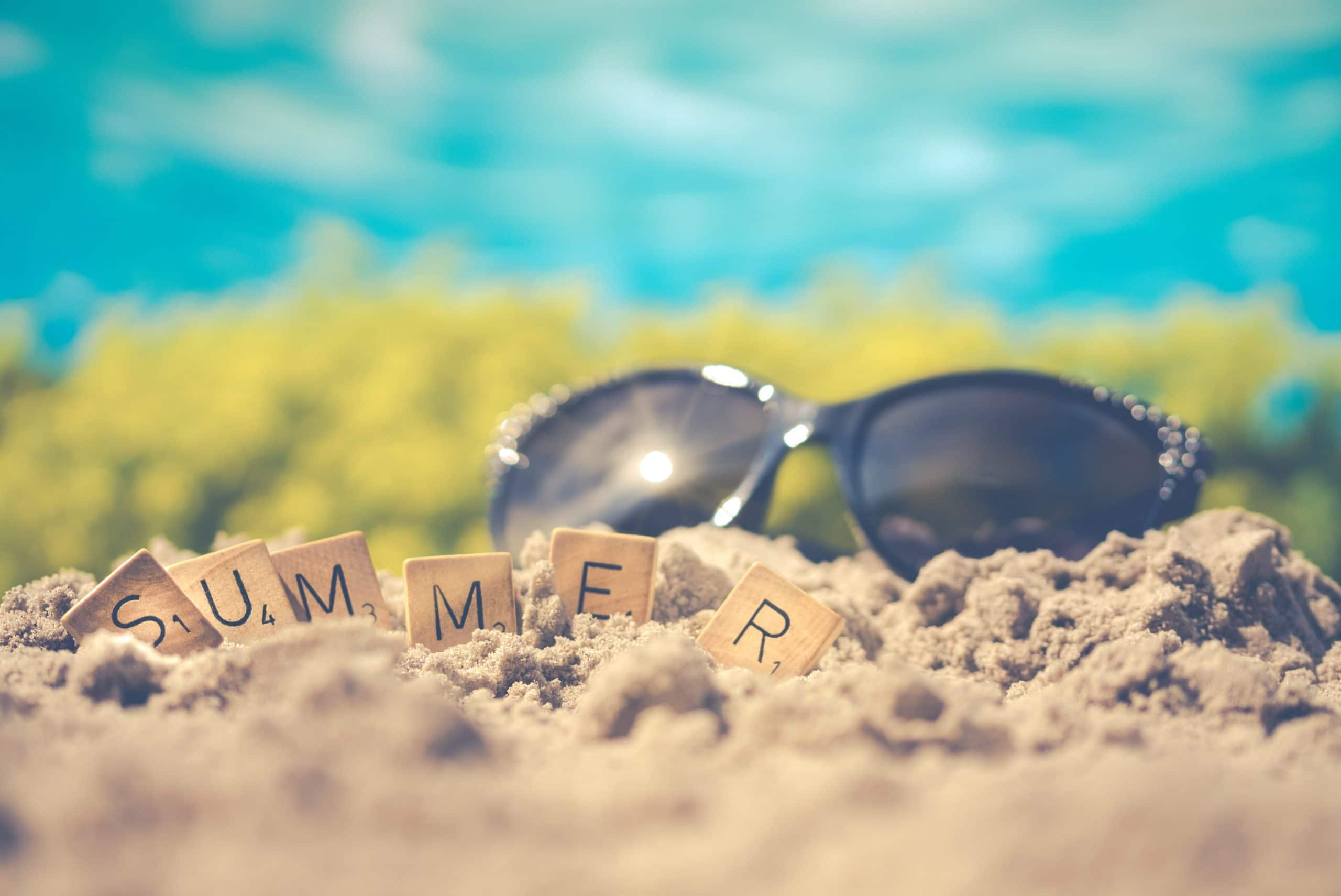 "Sunglasses on sand with letters spelling ""summer"""