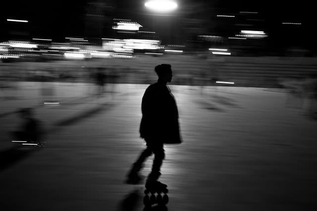Black and white photo of inline skater with motion blur