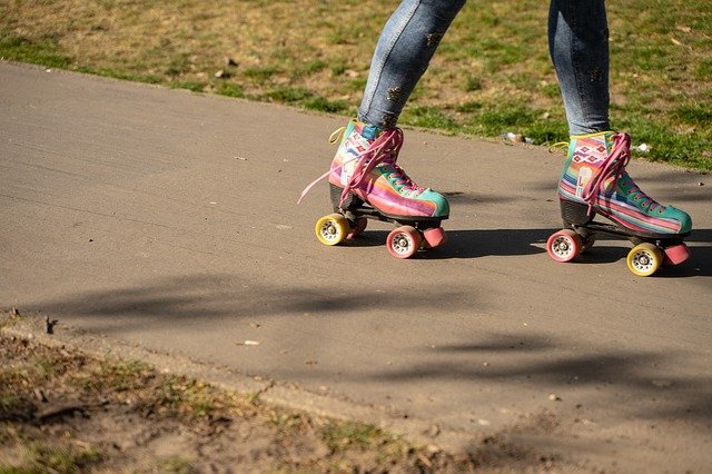 Ankle down shot of girl skating on sidewalk with colorful roller skates