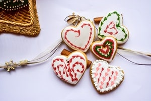 Flatlay photo of holiday heart cookies on white background