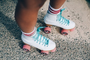 Photo of person wearing white roller skates with pink wheels