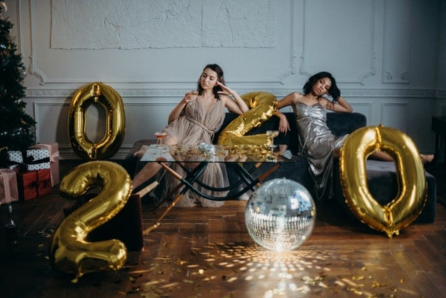 Bored women lounging on couch in room with 2020 balloons and mirror ball