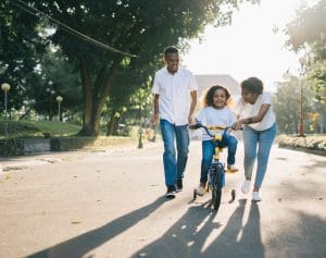 Parents teaching child how to ride bike