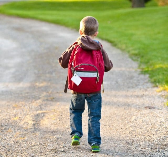 Small child with red backpack walking to school