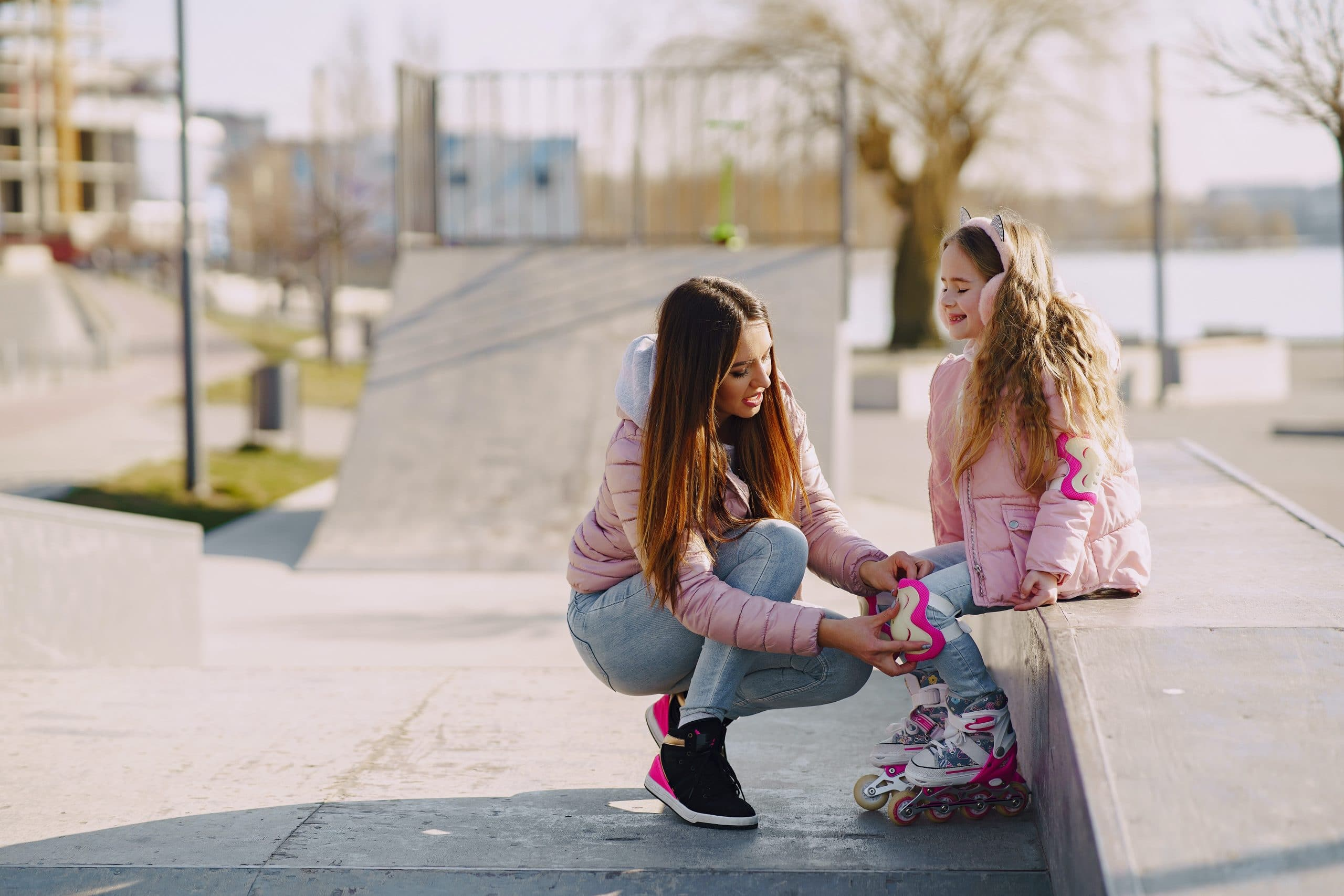 Stylish mom putting knee pads on daughter for roller skating