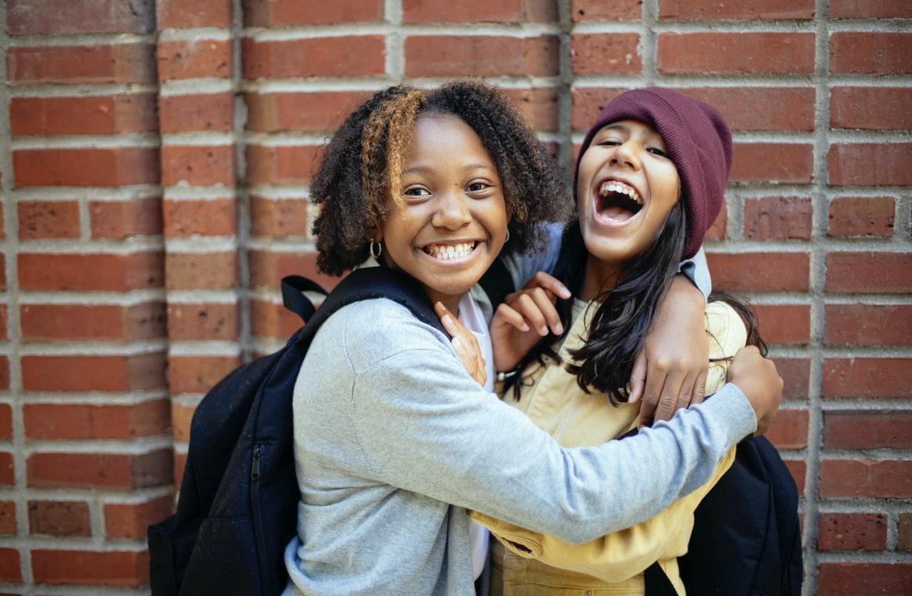 Happy schoolgirls hugging in front of brick wall