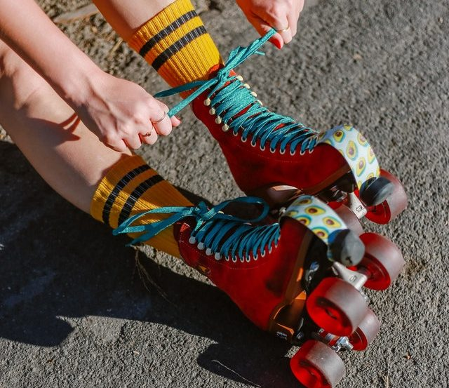 Person tying laces of colorful roller skates