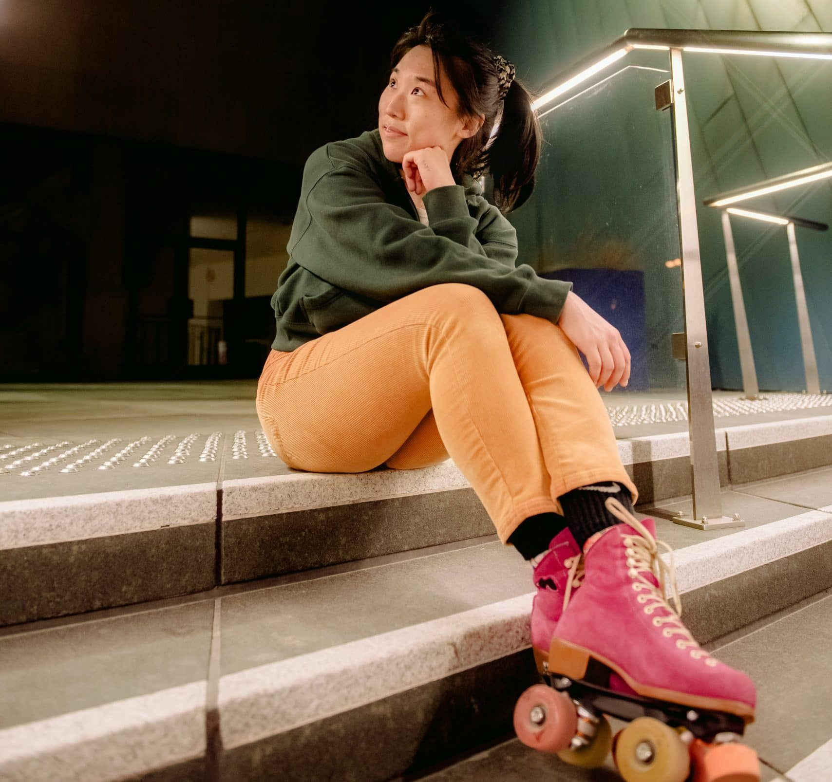 Stylish young woman in pink and orange quad skates sitting on steps