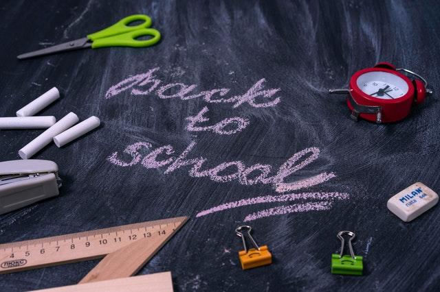 "Blackboard with ""Back to school"" written in chalk with school supplies"
